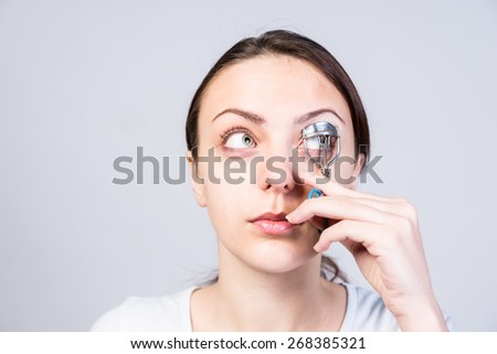 Close up Young Woman Curling her Eyelashes Using a Tool While Looking Up Seriously on a Light Gray Background. - stock photo
