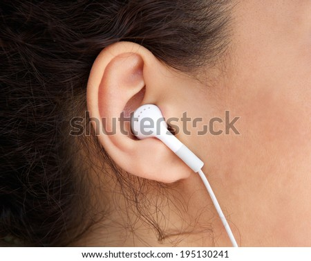 Close up young woman ear with earphone  - stock photo