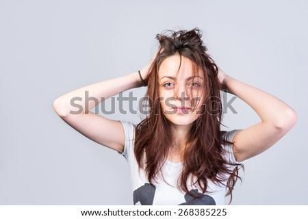 Close up Young Woman Holding her Long Messy Hair While Looking at Camera Seriously on a Gray Background. - stock photo