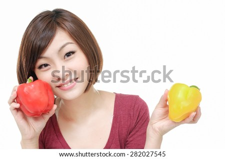 Close up young woman holding red and yellow paprika - stock photo