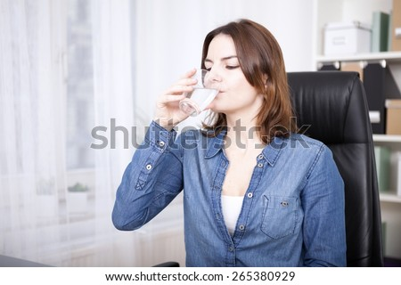 Close up Young Woman in Denim Long Sleeves Shirt Sitting on Office Chair While Drinking a Glass of Water - stock photo