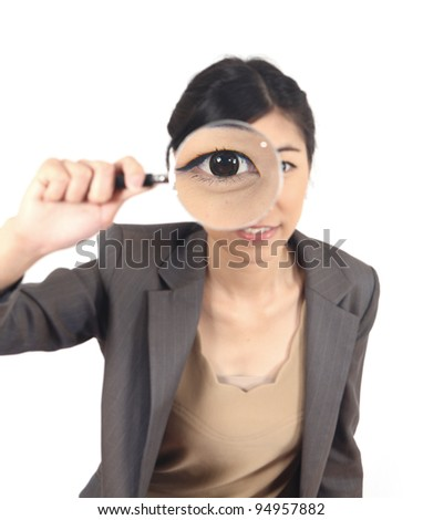 close-up young woman looking through a magnifying glass isolated - stock photo