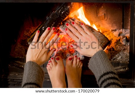 close up young woman warming her feet and hand in front of an open fire.  - stock photo
