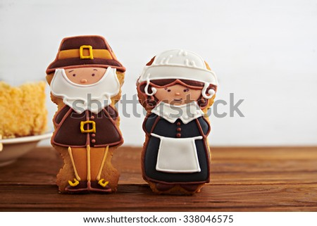 Close view at figures of gingerbread pilgrims with Thanksgiving pumpkin pie on a back on a wooden background - stock photo