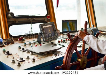 Close view into captain's cabins, navigation equipment and captain's hand on rudder during cruising  - stock photo