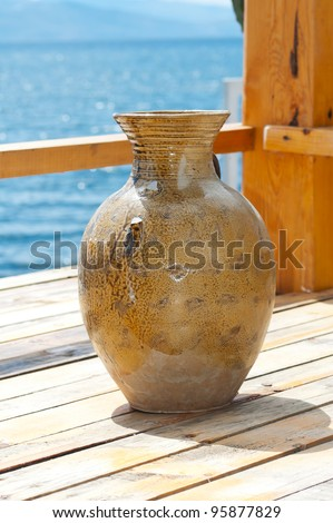 Close view of a ceramic vase on a table in front of the ocean - stock photo