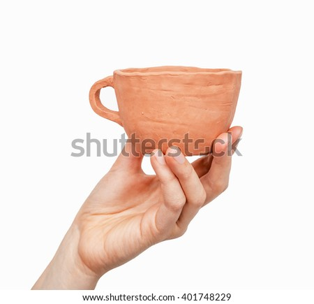 Close view of a clay cup in a woman's hand isolated on white background - stock photo