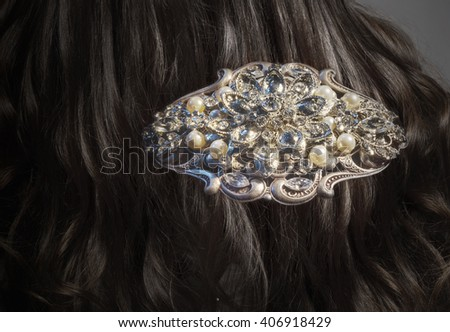 Close view of a fancy diamond brooch with pearls in brunette's hair - stock photo