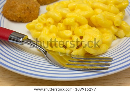 Close view of a meal of chicken nuggets with macaroni and cheese on a plate with fork. - stock photo