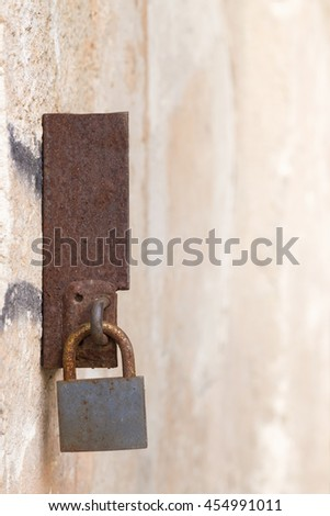 Close view of a rusty lock on a rusty metal on a wall - stock photo