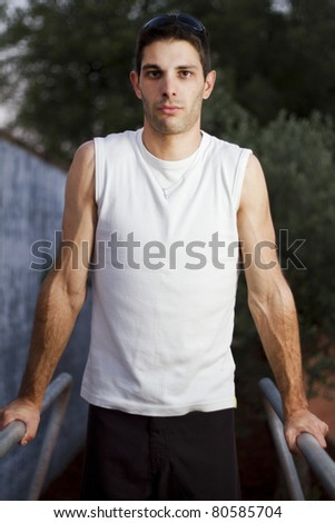 Close view of a young man doing exercise on a park. - stock photo