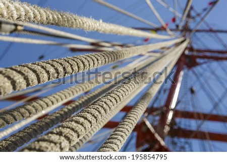 Close view of aged rope rigging of a tall ship sailing mast over blue clear sky. Shallow depth of field with upward perspective. - stock photo