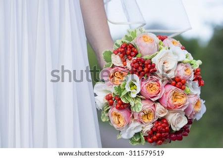 Close view of beautiful colorful wedding bouquet in a hand of a bride - stock photo