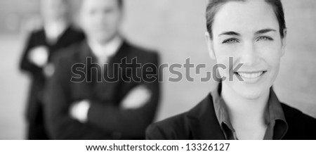 close view of businesswoman and businessmen standing in a row smiling - stock photo