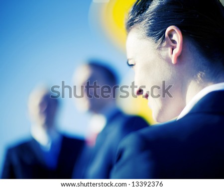 close view of businesswoman looking forward with businessmen standing in front - stock photo