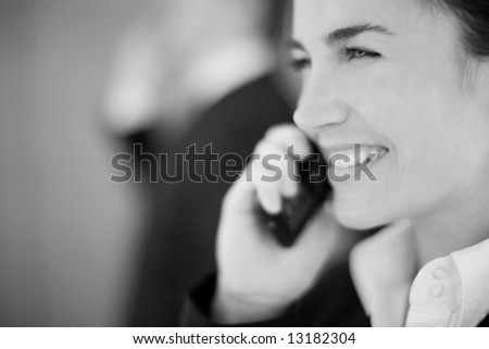 close view of businesswoman smiling with cellphone next to face - stock photo