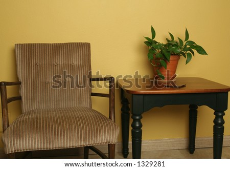 Close view of classic chair and table against gold wall - stock photo
