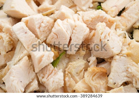 Close view of cut up chicken breast for salad with spinach. - stock photo
