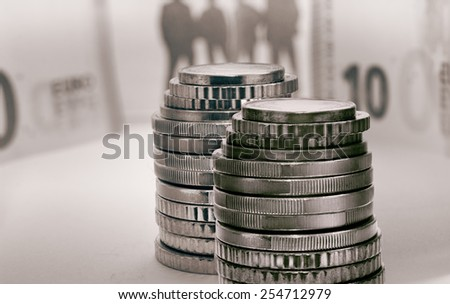 Close view of euro coins and blurry banknotes and people silhouettes in monocolour - stock photo