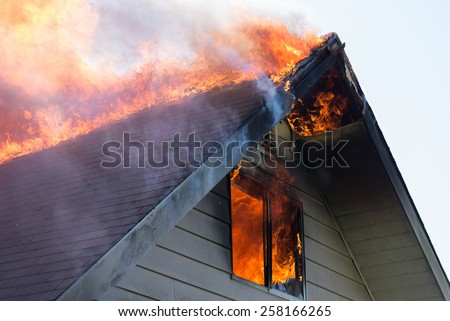 Close view of flames in an upper story window and running across the roof ridge. - stock photo