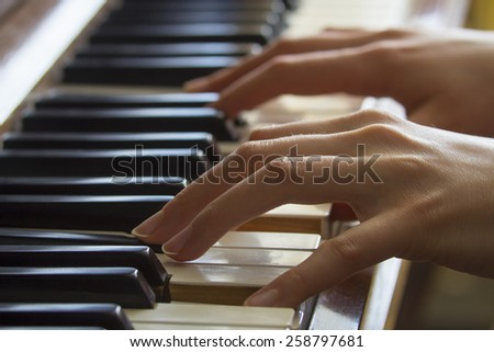 Close view of girl's hands on acoustic piano - stock photo