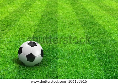 Close view of green striped football field with soccer ball - stock photo
