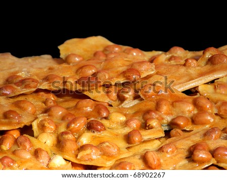 Close view of peanut brittle against black background.