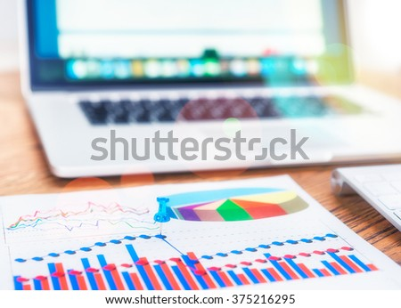 Close view of pin on the graph chart. Laptop with business data on background. - stock photo