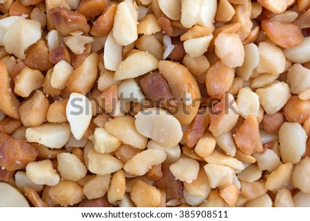 Close view of roasted and salted macadamia nut pieces illuminated with natural light.