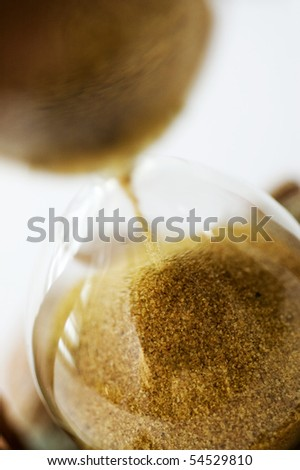Close view of sand flowing through an hourglass. Focus is  down on the sand with reflection on hourglass. The background is white. - stock photo