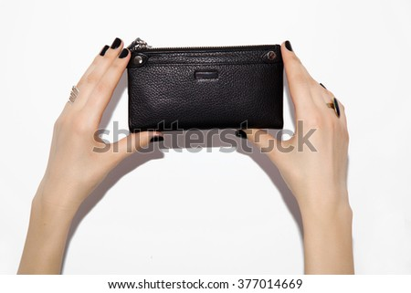 Close view of stylish and fashionable girl accessories. Two hands with black nails holding a black leather clutch on white background.