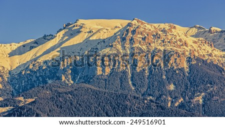 Close view of sunlit Bucegi mountains ridge with steep slopes covered by snow at sunset, Carpathians mountains range, Romania. - stock photo