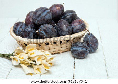 Close view of tasty purple plums isolated on a white wooden background. - stock photo