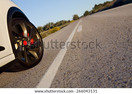 Close view of the wheel of a withe sport car on a road.  Wheel on a road.