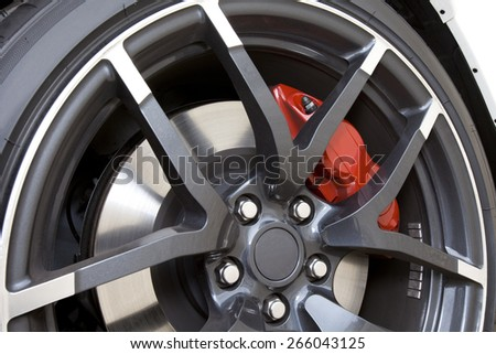 Close view of the wheel of sport car with red brake caliper. Aluminum Rim.