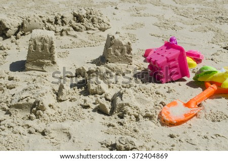 Close view of two sand castles and bright-colored children beach toys on the sand - stock photo