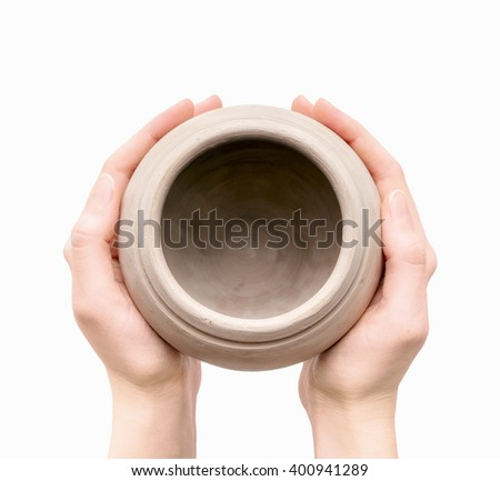 Close view of unburnt clay pot in a woman's hands isolated on white background - stock photo