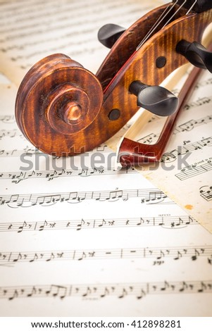 Close view of violin scroll and bow on musical sheet - stock photo