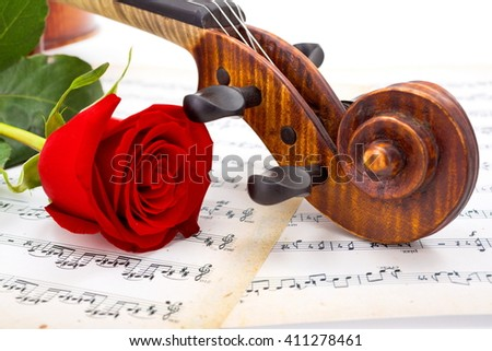 Close view of violin scroll and red rose on musical sheet - stock photo