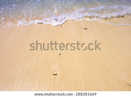 Close view of wave lapping on shore of tropical sandy beach - stock photo