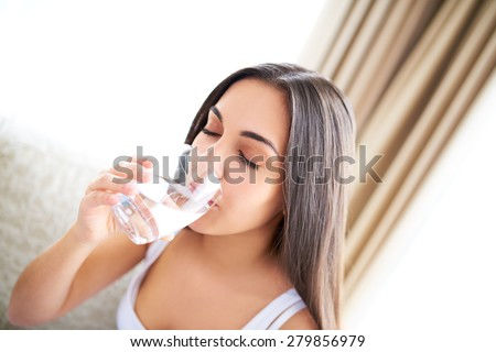 Close view of woman drinking glass of water with eyes closed sitting on couch. - stock photo
