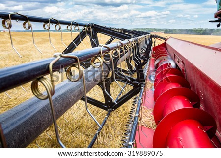 Close view on the combine working on the wheat field - stock photo