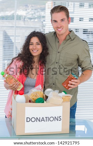 Close volunteers taking out food from donations box for a charity - stock photo