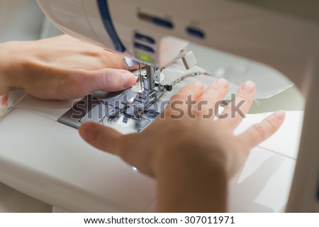 close woman hands sewing on sewing machine