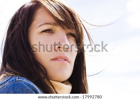 Close woman portrait with her hair on the wind. - stock photo