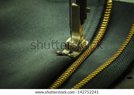 Close-zipper and a sewing needle. - stock photo