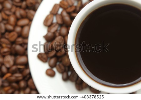 closecup on cup of coffee with roasted coffee - stock photo
