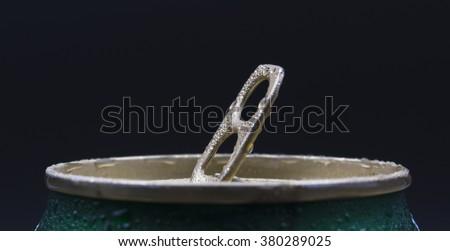 Closed aluminium can pull ring. Dark background. - stock photo