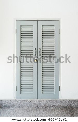 Closed and locked gray wood door , locked window in white wall background, security concepts