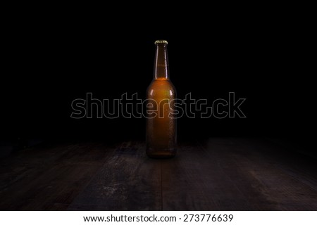 Closed beer bottle on a rustic table - stock photo
